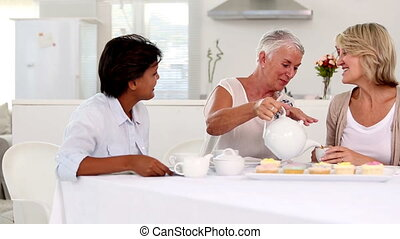 Mature woman pouring tea to her friends cup for the tea...