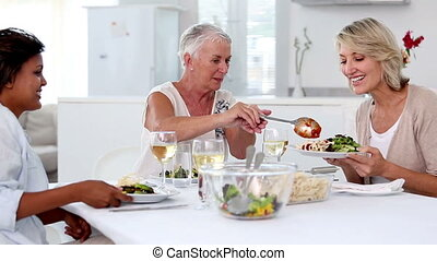 Woman offering meal to her friends in the dinning room