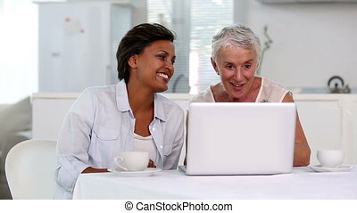 Two mature women looking at laptop then laughing together