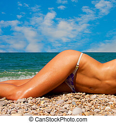 A woman sunbathes on a beach - A girl with a beautiful...