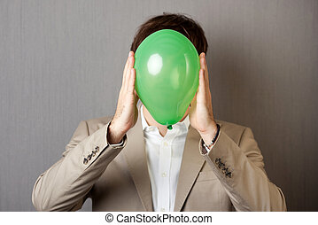 Businessman Holding Balloon In Front Of Face - Young...