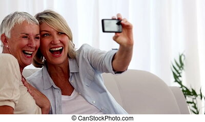 Women taking pictures together while they are sitting on the...