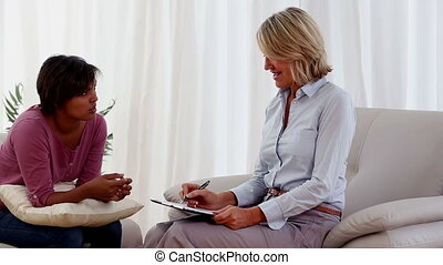 Woman sitting on sofa talking to therapist who is taking...