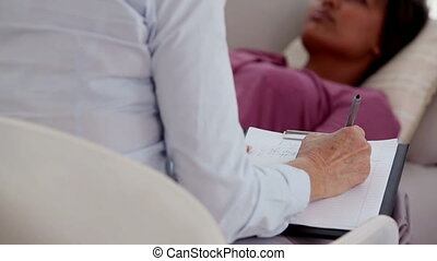 Patient lying on sofa in therapy with therapist taking notes