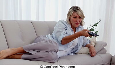 Woman lying on her sofa and watchin - Blonde woman lying on...