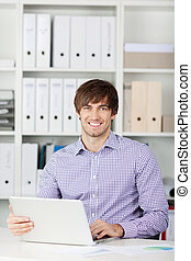 Smiling Businessman Using Laptop In Office
