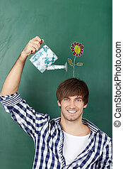 Portrait of handsome young male student holding watering can with flower drawn on chalkboard representing growth of ideas