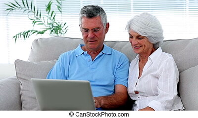 Retired couple using laptop together on the couch at home