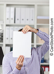 Businessman Holding Blank Paper In Front Of Face In Office -...