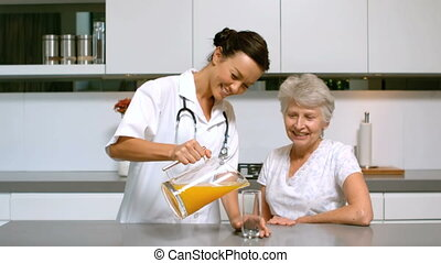 Home nurse pouring orange juice for patient in kitchen in...