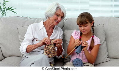 Granny teaching her granddaughter how to knit at home on the...
