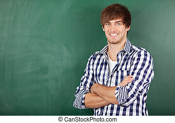 Male Teacher With Arms Crossed Standing Against Chalkboard -...