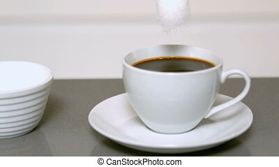 Sugar pouring into cup of coffee
