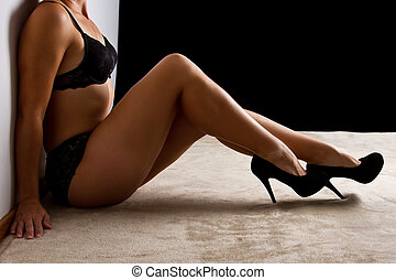 Woman in black underwear sit on floorl shoes