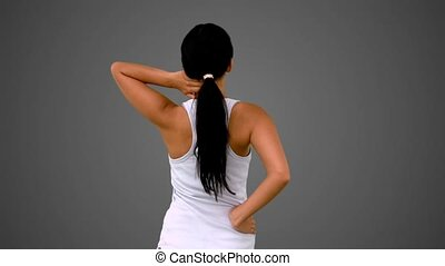 Fit brunette stretching her back and neck on grey background...
