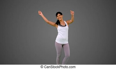 Fit brunette dancing and smiling on grey background in slow...