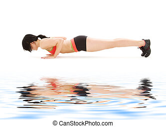 woman practicing four-limbed staff pose - woman practicing...