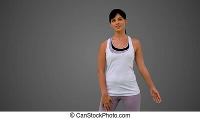 Fit brunette stretching arm on grey background in slow...