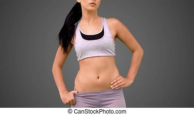 Fit brunette shaking her hair on grey background in slow...