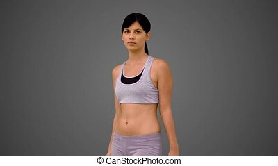 Fit brunette making martial arts pose and smiling on grey...