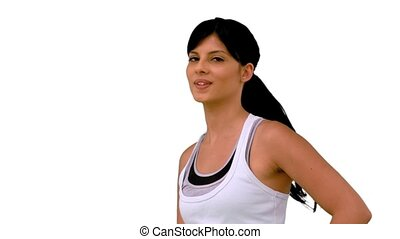 Fit woman tossing her hair and smiling on white background...