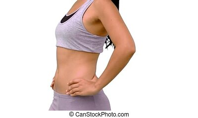 Fit woman turning to camera on white background in slow...
