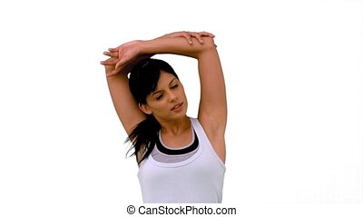 Fit woman stretching out her arms on white background in...