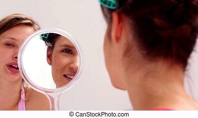 Girl wearing rollers looking in mir