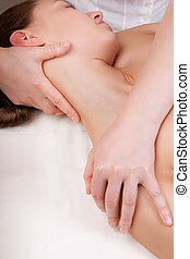 Therapist doing massage on a womans neck by extending neck...