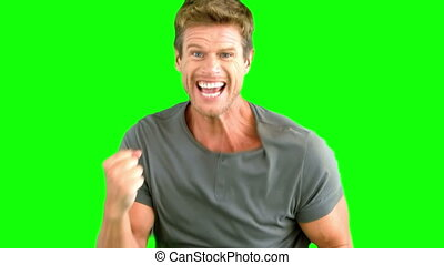 Attractive man gesturing and showing his happiness on green...