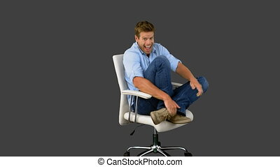 Smiling man cheering and turning on swivel chair on grey...