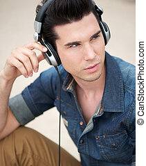 Portrait of a handsome young man listening to music with headphones