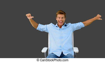 Man on swivel chair giving thumbs up on grey screen in slow...