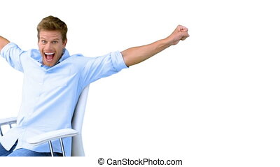 Man on swivel chair raising arms to show his success on...