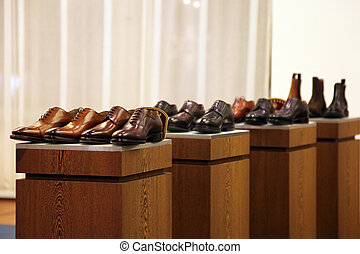 Mens shoes in a store display arranged in neat rows on top...