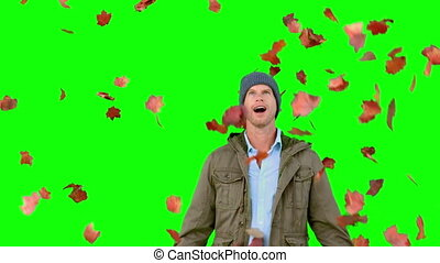 Amazed man looking at falling leaves on green screen in slow...