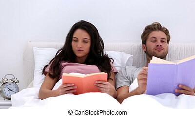 Couple reading books at home in bed