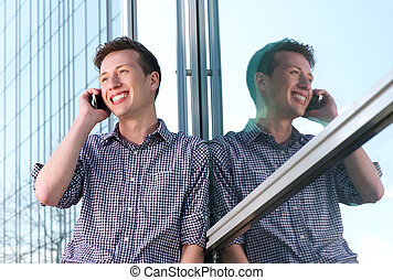 Handsome young man calling on mobile phone outdoors
