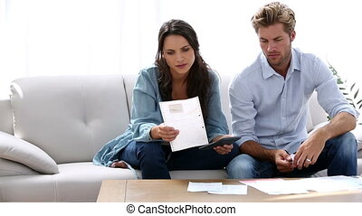 Couple working out their finances at home on the couch