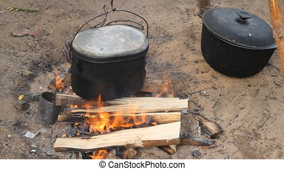 cooking in a kettle - kettle on fire in a camping