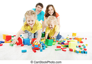 Happy family. Parents with two kids playing blocks over white