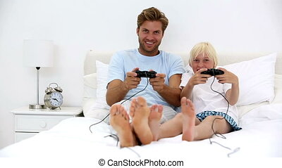 Father and son playing video games together at home on bed
