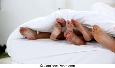 Family kicking their feet under the covers at home in bed