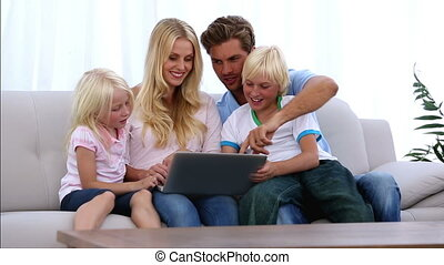 Family using laptop together at home on the couch