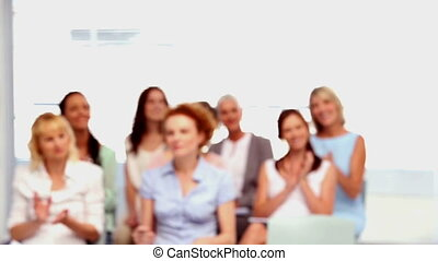 Buisnesswomen applauding colleague who is smiling at the...