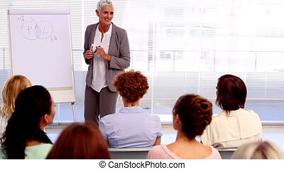 Businesswoman giving a lecture to other businesswomen in the...
