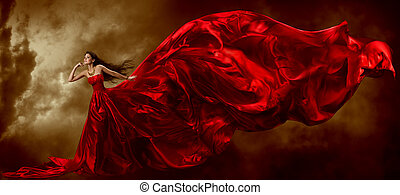 Woman in red waving beautiful dress with flying fabric over...