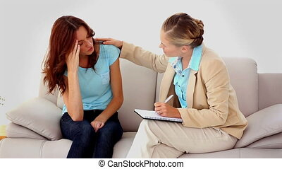 Woman getting upset talking to a therapist who is comforting...