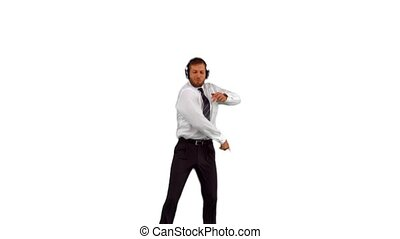 Businessman jumping up and dancing while listening to music...