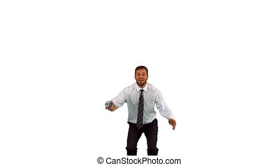 Businessman jumping up holding alarm clock in slow motion